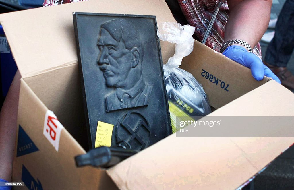Policemen confiscate objects, among them a portrait of Adolf Hitler, from the residence of a member of the right-extremist 'Kameradschaft Aachener Land' association on August 23, 2012 in Juelich, western Germany. North Rhine-Westphalia's Interior Minister banned several right extremist comradeships in the western federal state. More than 900 policemen searched around 120 houses and appartments across the state. AFP PHOTO / RALF ROEGER GERMANY OUT