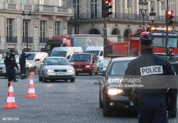Policemen control motorists driving on the Place de la Concorde on the implementation day of a traffic restricted area in Paris on January 18 2017 /...