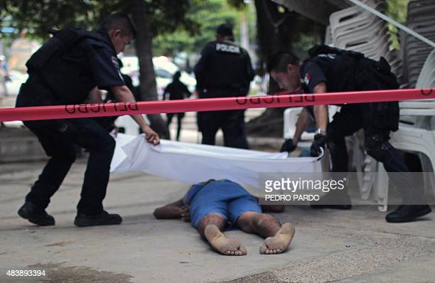 Policemen cover the body of a man slain during a shooting in the tourist zone of Acapulco Guerrero State on August 13 2015 AFP PHOTO / PEDRO PARDO