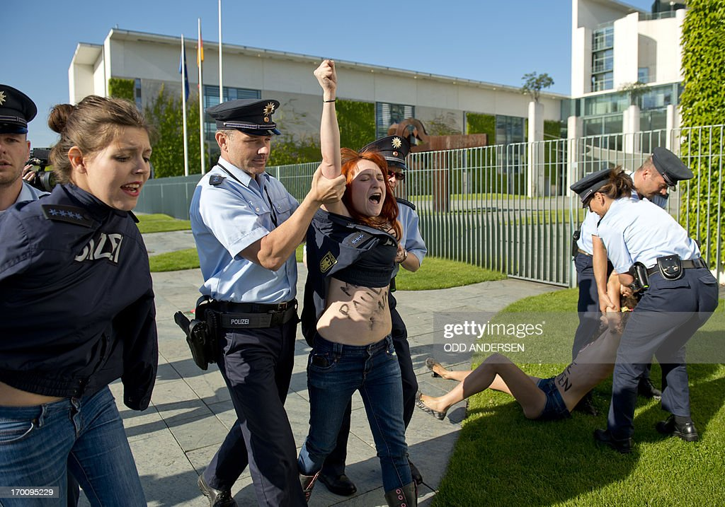 Policemen cover up with their uniforms topless activists from the women's rights group FEMEN and march them off as they shout 'Merkel Free Femen' during a protest against Tunisian prime minister Ali Larayedh outside the Chancellery prior to Germany's Chancellor Angela Merkel's meeting with Larayedh in Berlin on June 7, 2013. The FEMEN action is held to support Amina Sboui, a young Tunisian arrested for an anti-Islamist protest inspired by topless protest group Femen.
