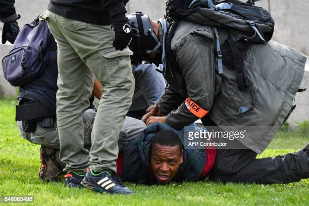 Policemen detain a demonstrator in Nantes western France during a protest called by several French unions against the labour law reform on September...