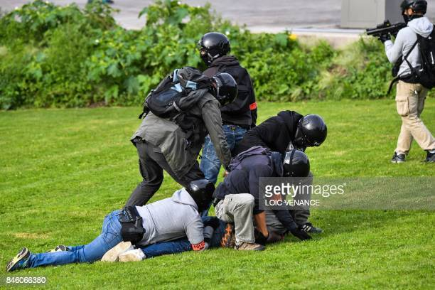 Policemen detain a protester during a protest called by several French unions against the labour law reform on September 12 2017 in Nantes western...