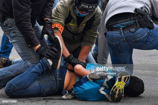 Policemen detain a protester during clashes within a protest called by several French unions against the labour law reform on September 12 2017 in...