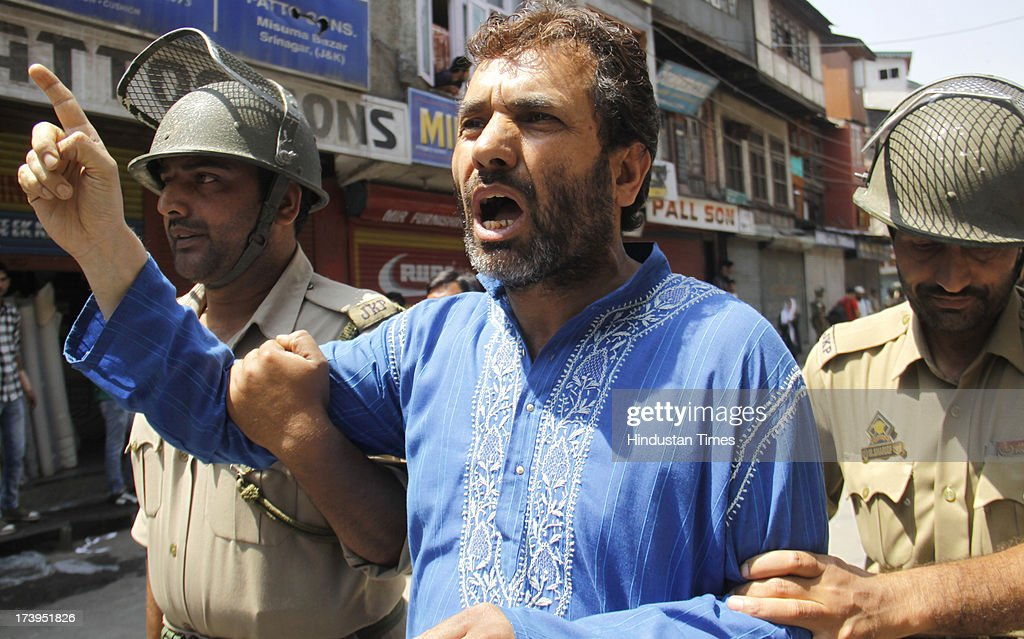 Policemen detain a senior leader of Jammu and Kashmir Liberation Front Javed Ahmad Mir during a protest against killing of 4 people in BSF firing on July 18, 2013 in Srinagar, India. Four people were killed today when security personnel opened fire at a mob that had gathered at a BSF camp in Ramban district protesting against alleged manhandling of an Imam of the area by the force. Curfew would be imposed in Srinagar and all other major towns in the Kashmir Valley from Friday morning as a precautionary measure.