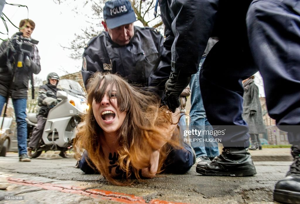 Policemen detain a topless Femen activist after she jumped in front of the car carrying former IMF chief Dominique Strauss-Kahn (not seen) upon his arrival for his trial in Lille, northern France, on February 10, 2015. Three topless women from the protest group Femen jumped on the car of Dominique Strauss-Kahn as the former IMF chief arrived to testify at his trial for 'aggravated pimping.' With slogans scrawled on their half-naked bodies and hurling insults at the car, the three protesters were quickly rounded up by police as the car entered an underground parking area.