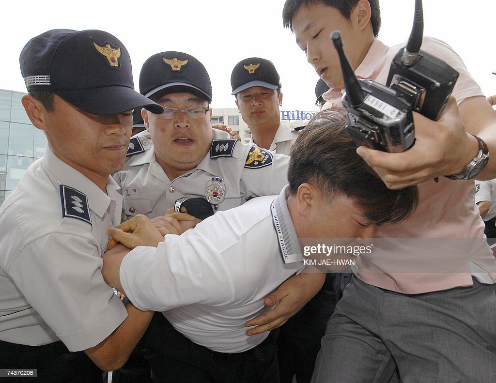 Policemen detain an activist from the South Korean People Representing Families Abducted by North Korea, after the activist and his colleagues entered a luxury hotel where inter-Korean ministerial talks were held, in Seoul 01 June 2007. The four-day meeting broke down over the delayed shipment of rice from South Korea. AFP PHOTO/KIM JAE-HWAN