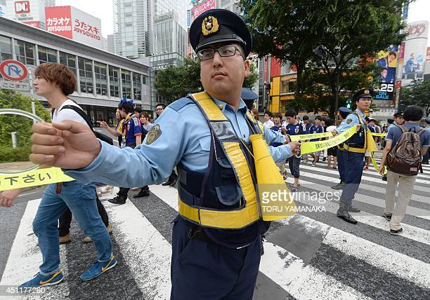 Policemen direct Japanese football fans leaving Shibuya shopping district in Tokyo on June 25 2014 after the FIFA World Cup group C match between...