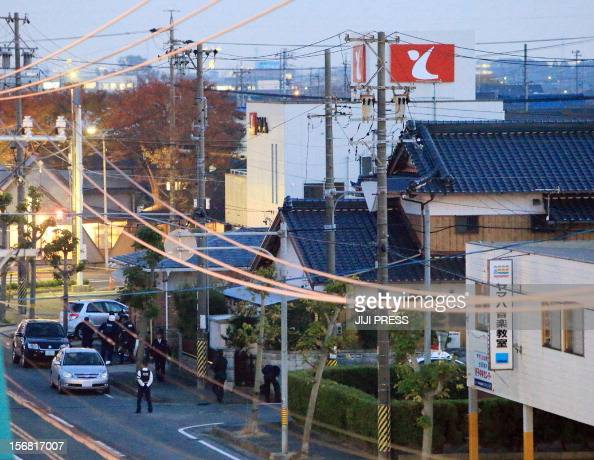 Policemen erect a cordon near a bank where a man was holding hostages in Toyokawa city in Aichi prefecture central Japan on November 22 2012 A...