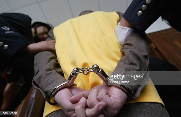 Policemen escort a handcuffed gang member during a trial at the Meishan Intermediate People's Court on October 12 2005 in Meishan of Sichuan Province...