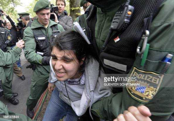 Policemen evacuate a young woman of Turkish origin who tried to get access to the Munich courthouse southern Germany on May 6 2013 upon the start of...
