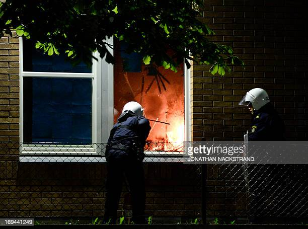 Policemen extinguish a burning school room in the Stockholm suburb of Tensta after youths rioted in few different suburbs around Stockholm and Sweden...