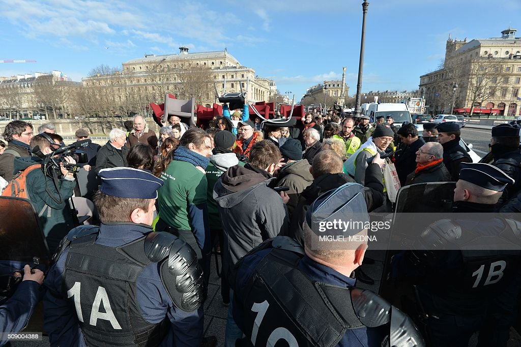Policemen face demonstrators carrying chairs taken from bank offices on February 8, 2016 on the pont au change near the Court of Paris during a demonstration against bank system and tax fraud, as former French budget minister Jerome Cahuzac goes on trial on February 8 for tax fraud. Cahuzac resigned in disgrace in 2013 after admitting to having a secret Swiss bank account, and faces up to seven years in jail and two million euros ($2.2 million) in fines. AFP PHOTO / MIGUEL MEDINA / AFP / MIGUEL MEDINA