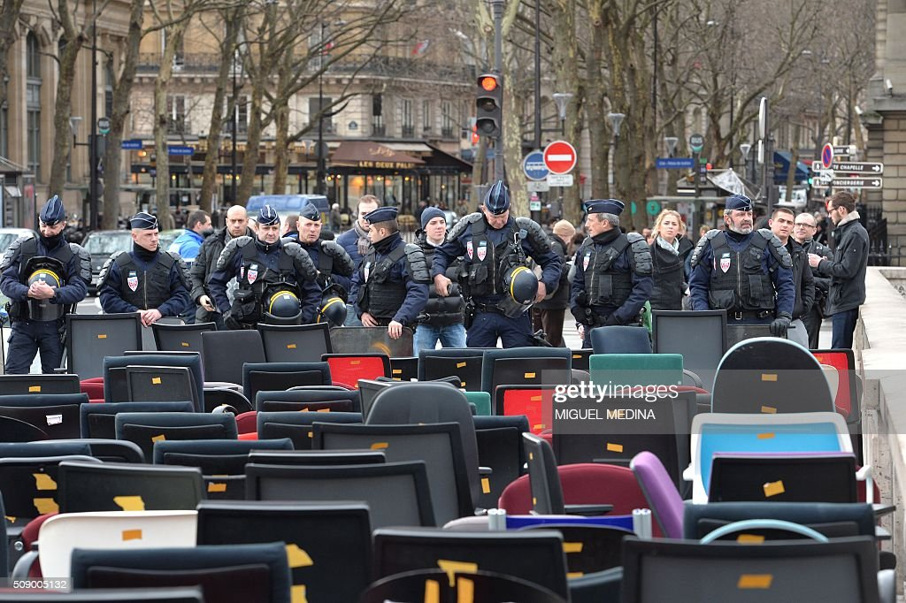 Policemen face empty chairs taken from bank offices on February 8, 2016 on the pont au change near the Court of Paris during a demonstration against bank system and tax fraud, as former French budget minister Jerome Cahuzac goes on trial on February 8 for tax fraud. Cahuzac resigned in disgrace in 2013 after admitting to having a secret Swiss bank account, and faces up to seven years in jail and two million euros ($2.2 million) in fines. AFP PHOTO / MIGUEL MEDINA / AFP / MIGUEL MEDINA