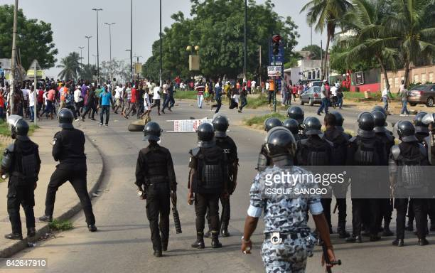 Policemen face protesters angry subscribers who invested in agribusiness companies during a demonstration on February 18 2017 in Abidjan after...