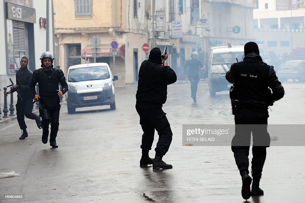 Policemen fired tear gas during clashes with protesters following a rallye outside the Interior ministry to protest after Tunisian opposition leader and outspoken government critic Chokri Belaid was shot dead, on February 6, 2013 in Tunis. The protesters, who massed on Habib Bourguiba Avenue, epicentre of the 2011 uprising that ousted ex-dictator Zine El Abidine Ben Ali, pelted the police with bottles and the police responded by firing tear gas, chasing the protesters and beating them with batons.