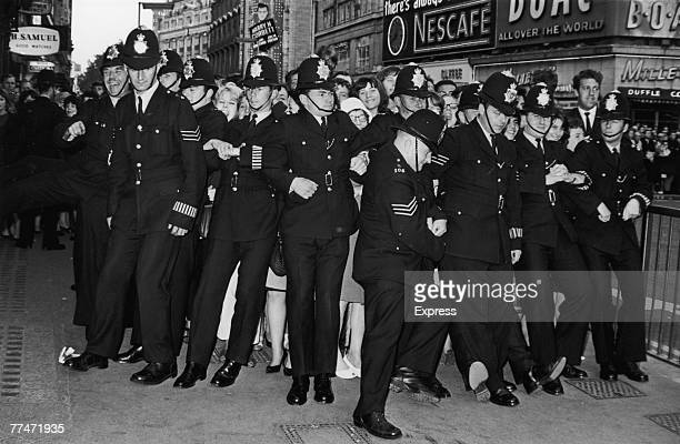 Policemen form a line to restrain female fans during the premiere of the new Beatles film 'Help' at the London Pavilion Piccadilly Circus 29th July...