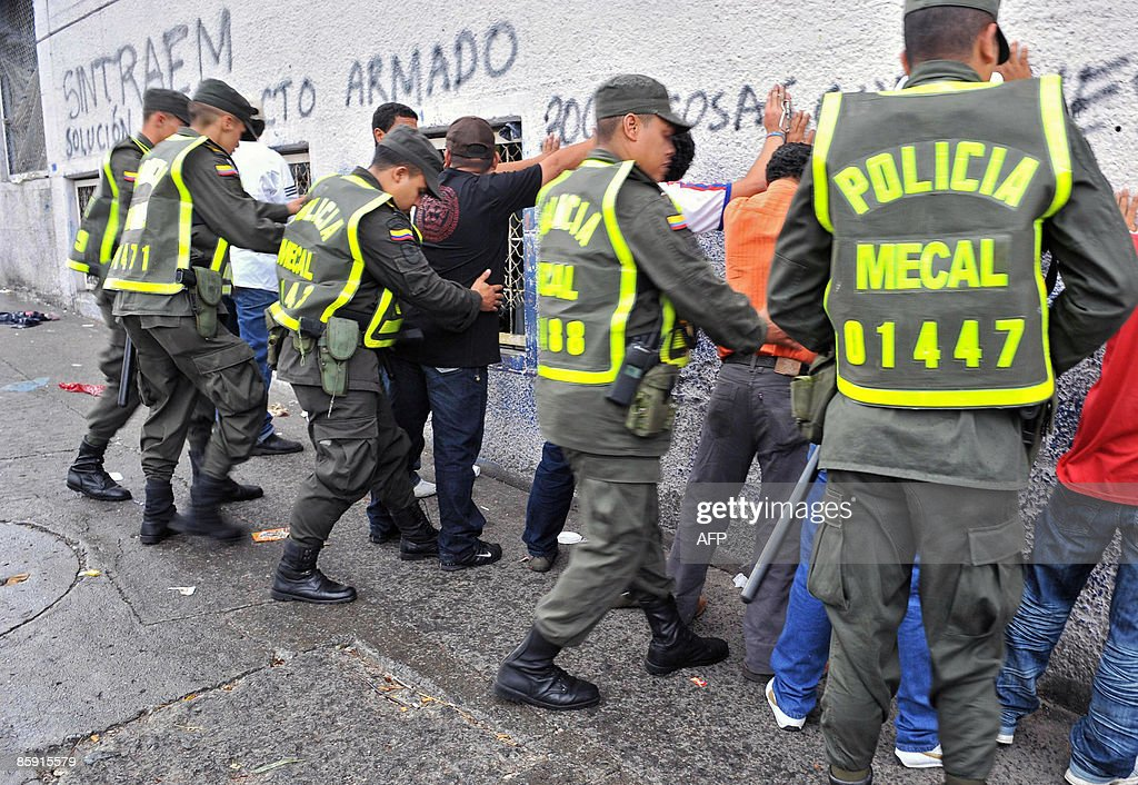 Policemen frisk suspects during an operation against crime on April 11 in Cali department of Valle del Cauca Colombia AFP PHOTO/Luis ROBAYO