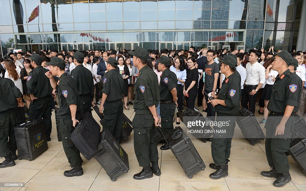 Policemen from a special forces unit pull suitcases while people wait to enter the National Convention Center where US President Barack Obama will deliver a live-broacast speech in Hanoi on May 24, 2016. US President Barack Obama told communist Vietnam on May 24 that basic human rights would not jeopardise its stability, in an impassioned appeal for the one-party state to abandon authoritarianism. / AFP / POOL / HOANG