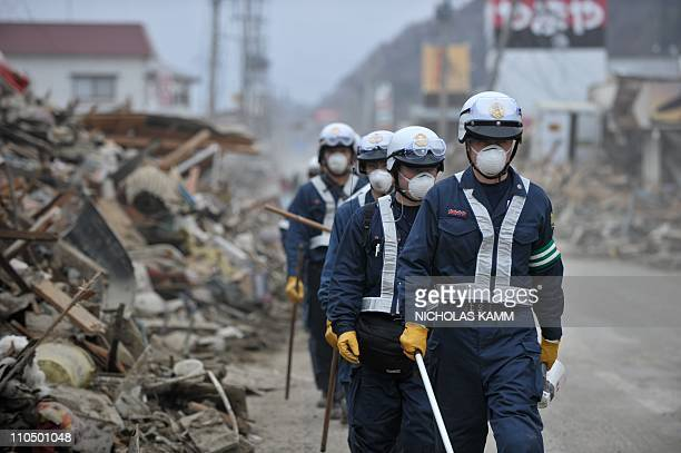 Policemen from Kobe walk down a street as they conduct rescue operations in the devastated city of Ishinomaki on March 21 2011 following the deadly...