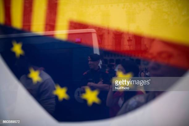A policemen from Mossos of Esquadra is seen through a Catalonian and Eu flag during a rally to mark Spain's National Day in Barcelona northeastern...