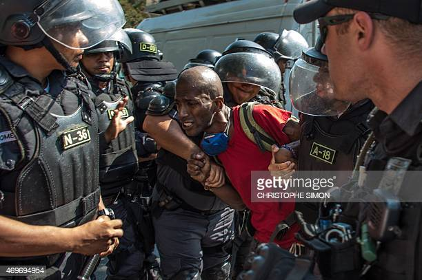 Policemen from the special unit CHOQUE arrest a squatter from the occupied building in Flamengo Rio de Janeiro on April 14 2015 More than 100...