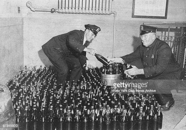 Policemen Goldinger and Faulkner check over 500 bottles of home brew seized in a Rockaway Beach speakeasy raid by men from the 15th Inspection...