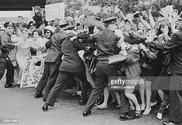 Policemen holding back excited Rolling Stones fans in New York where the band are on tour June 1964