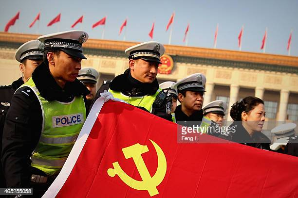 Policemen holding the flag of China's Communist Party pose for photos during the opening session of the National People's Congress at the Great Hall...