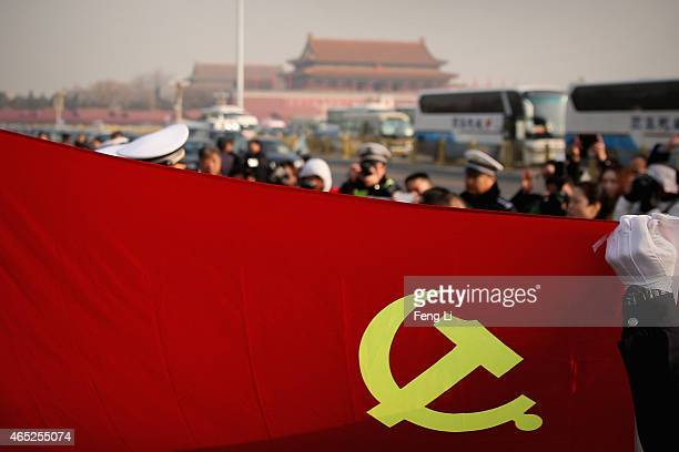 Policemen holding the flag of China's Communist Party pose for photos during the opening session of the National People's Congress at the Tiananmen...