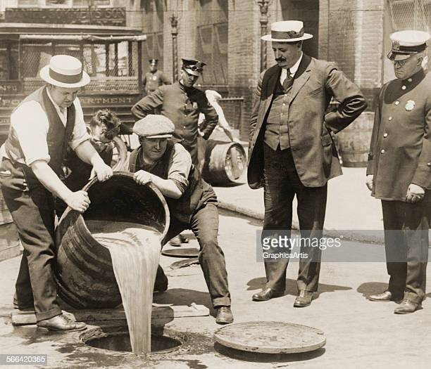 Policemen in New York City pour liquor from a barrel down a sewer in a raid during Prohibition photograph 1921