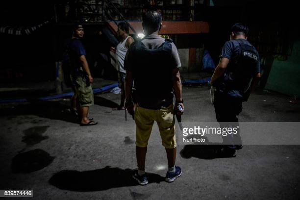 Policemen in plainclothes patrol a dark alley near the scene where 3 men were killed during a police operation against illegal drugs in Caloocan...