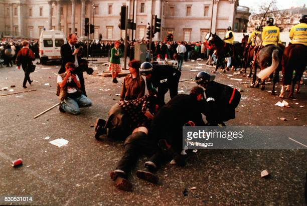 Policemen in riot gear attend to one of the casualties of the riot which developed out of a demonstration against the socalled Poll Tax in Trafalgar...