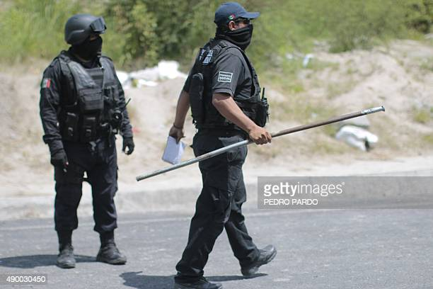 Policemen inspect a bus transporting students of Ayotzinapa as they go to school in Tixtla Guerrero State Mexico on September 25 2015 The students...