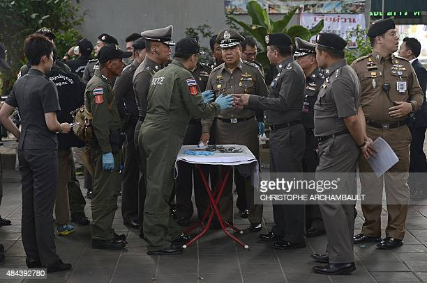 Policemen inspect metal pieces collected as evidence at the site of an explosion near a busy train station in central Bangkok on August 18 2015 A...