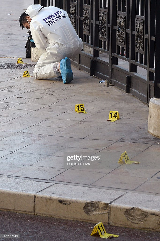 Policemen investigate near the Marseille's Opera (unseen), southern France, on the site where two men were injured after gunshots on September 1, 2013. AFP PHOTO / BORIS HORVAT