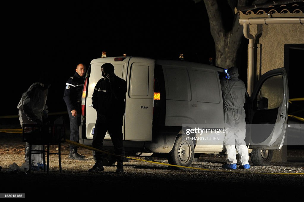 Policemen investigate near the vehicle where a man was shot dead earlier in front of his restaurant, on January 3, 2013 in Trets, south eastern France.