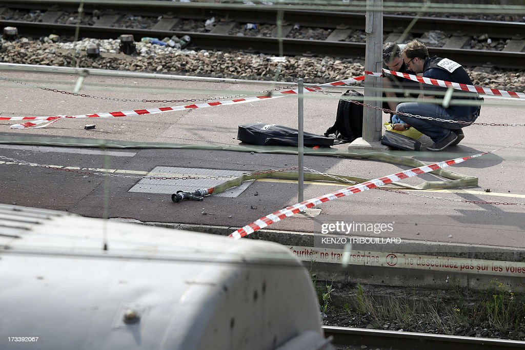 Policemen investigate on the site of a train accident on July 13, 2013 at the railway station of Bretigny-sur-Orge, near Paris. At least six people were killed and dozens injured yesterday after a speeding train derailed at a station in the southern suburbs of Paris, officials said.