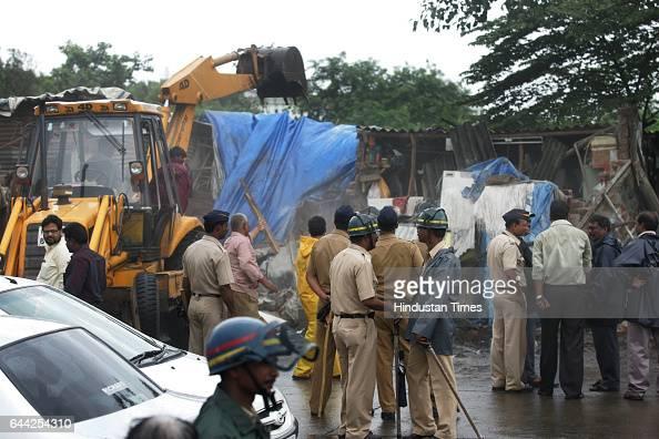 Policemen keep a watch as municipal workers demolish illegal shops on the Kalina University Road at Santacruz