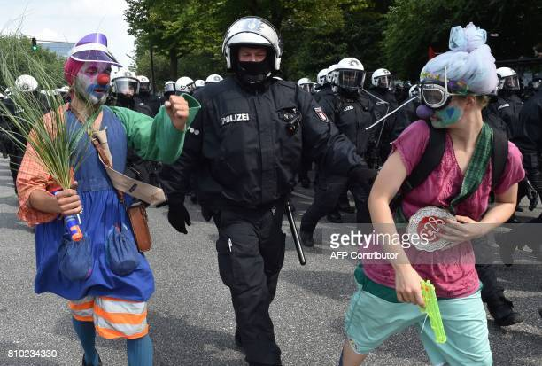 Policemen lead away demonstrators dressed as clowns during a protest on July 7 2017 in Hamburg northern Germany where leaders of the world's top...