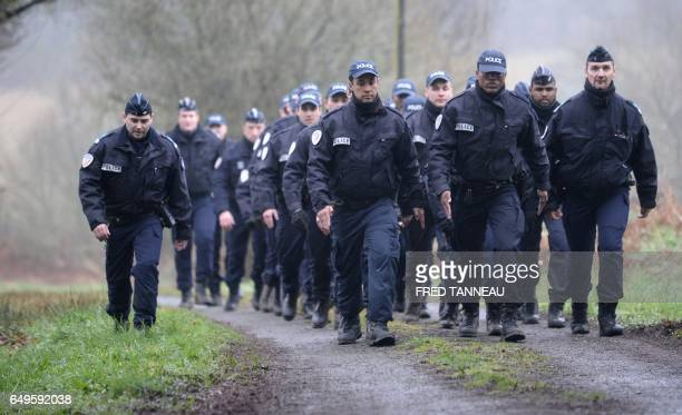 Policemen leave the house of the main suspect in the Troadec case Hubert Caouissin on March 8 2017 in PontdeBuis western of France Investigators on...