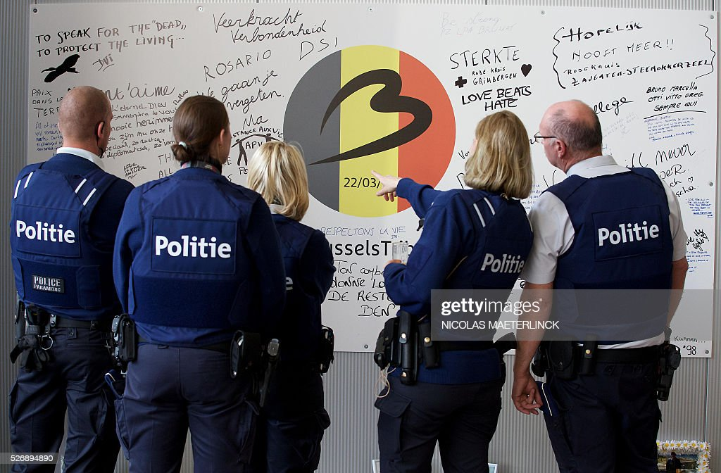 Policemen look at a wall with signatures of airport workers on May 1, 2016 after the opening ceremony of the departure hall, closed since the March 22 attacks, at Zaventem airport in Brussels. Brussels airport was hit on March 22, 2016 by one of the three Islamic State suicide bombers who struck the airport and Maelbeek - Maalbeek metro station on March 22, killing 32 people and injuring hundreds. MAETERLINCK / Belgium OUT