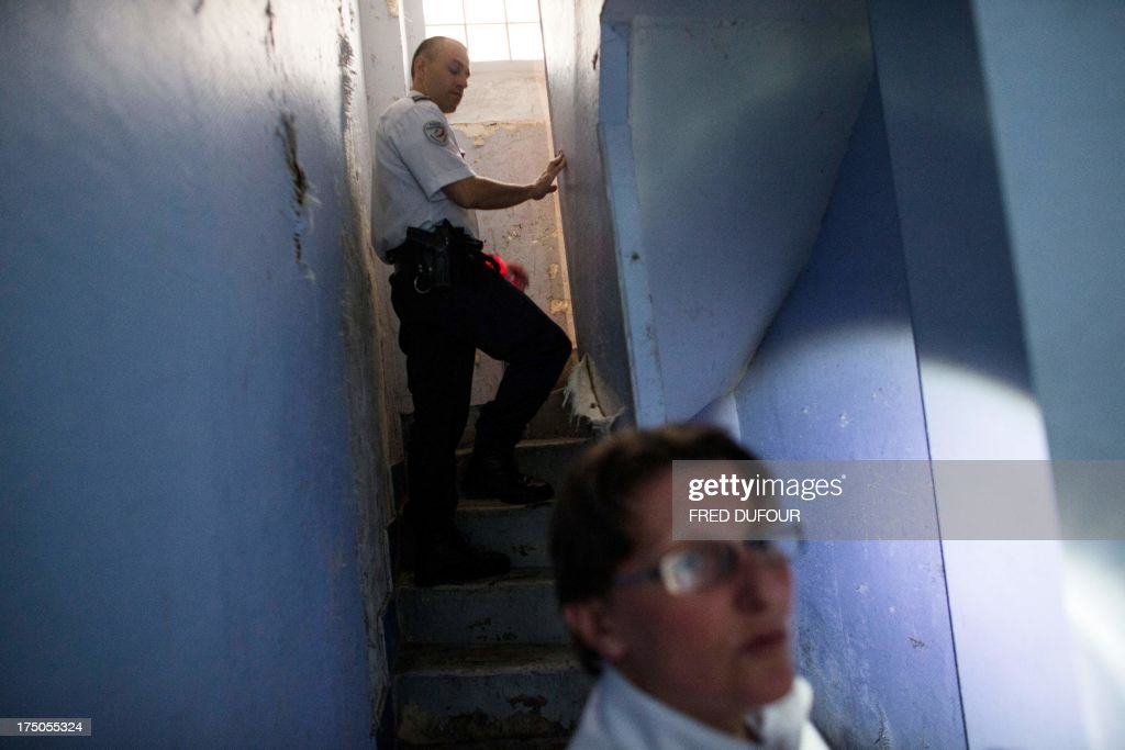 Policemen look for drug as they patrol in a building in a priority security zone (ZSP) in Saint-Denis, a Paris suburb on July 30, 2013.