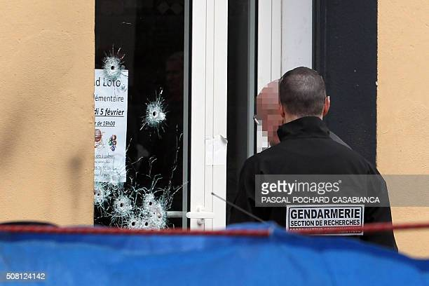 Policemen look for evidence at a Muslim butcher's shop that was sprayed with bullets overnight on February 3 2016 in Propriano on the French...