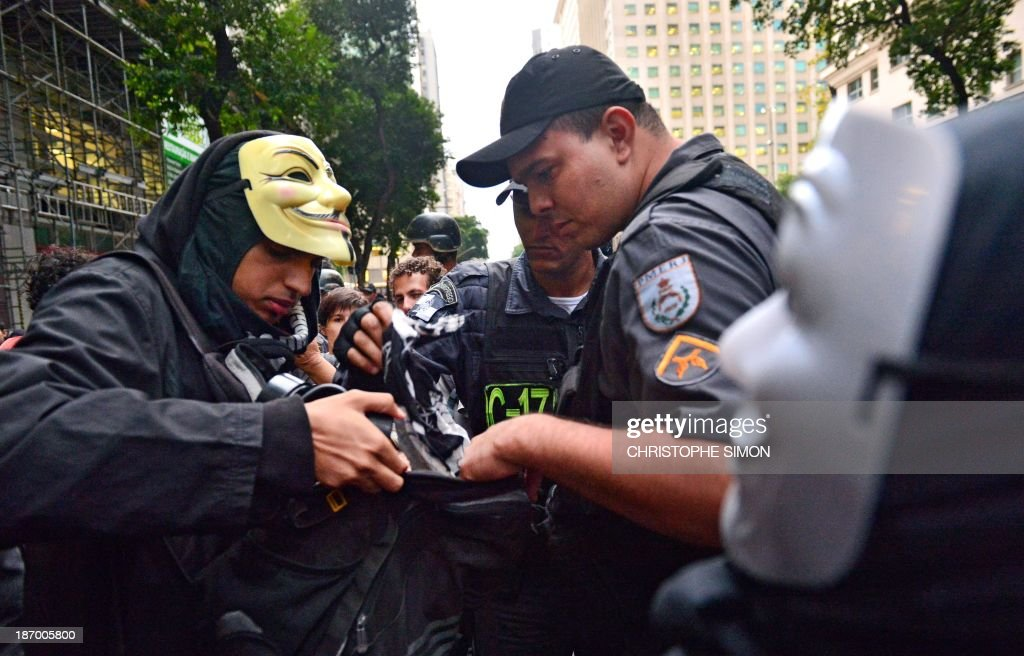 Policemen look into the backpack of a man wearing a Guy Fawkes' mask in Rio de Janeiro, Brazil on November 5, 2013, during a demonstration for the Guy Fawkes World Day. The demo was called by Brazilian Anonymous and Black Blocs social networks, which took it as the World Day of Resistance and Popular Rebellion. AFP PHOTO / CHRISTOPHE SIMON