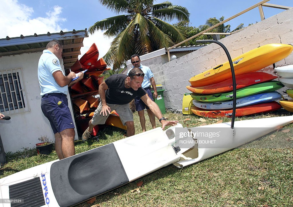 Policemen make a report near the pirogue damaged by a shark attack off La Houssaye cape on October 5, 2011 in Saint-Paul de la Reunion at the French overseas island of La Reunion. The kayaker, Jean-Paul Castellani was not hurt. Four shark attacks have been registered this year on the island, killing to people. Only one shark was captured during a three day track operation last September at La Reunion.