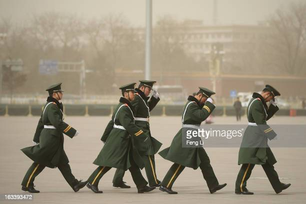 Policemen march on the Tiananmen Square during the sandstorm on March 9 2013 in Beijing China Strong winds dispersed Beijing's lingering haze but...