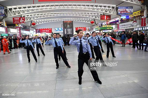 Policemen of Shenyang Railway perform during a flash mob at the waiting hall of the railway station on January 24 2016 in Shenyang Liaoning Province...