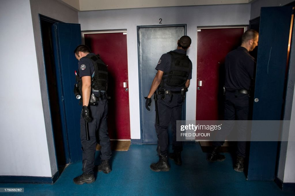 Policemen open doors and look for drugs in a building on July 30, 2013 in an area of ??priority security (ZSP) in Saint-Denis, a Paris suburb.