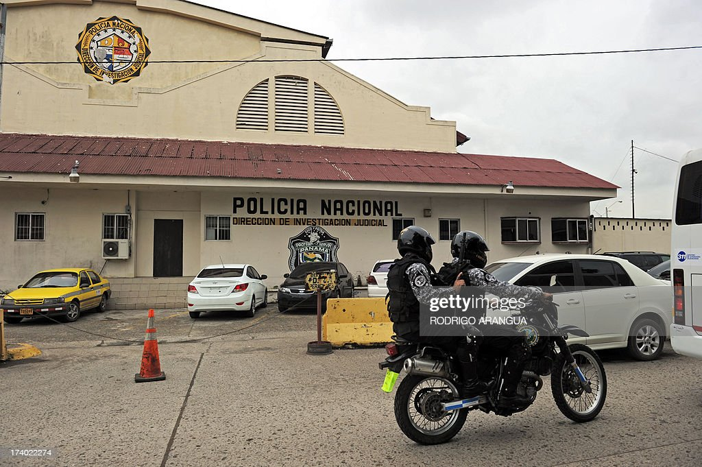 Policemen pass on a motorcycle in front of the National Police of Panama (DIJ) headquarters in Panama City on July 19, 2013. According to the Italian Ministry of Justice, Robert Seldon Lady aka 'Mister Bob', former head of the CIA in Milan, was arrested in Panama. AFP PHOTO / Rodrigo ARANGUA