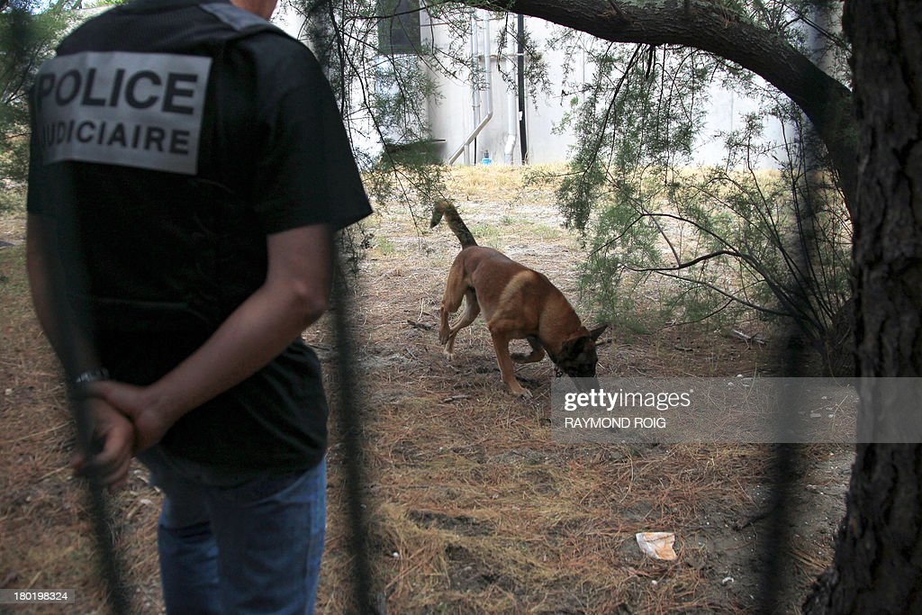 Policemen patrol assisted by a dog during a search as part of the inquiry into the disappearance of Marie-Josee and Alisson Benitez, a mother and her daughter, both missing since July 14, on September 10, 2013 at a treatment plant in Leucate, southern France. AFP PHOTO / RAYMOND